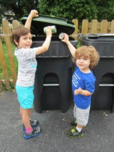 Two children helping their community as they put recycling in the recycling bin.