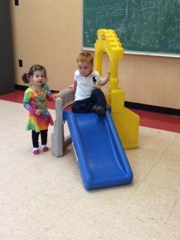 An image of two children playing on a slide together. One is going down the slide, and the other is patiently waiting her turn. They are enthusiastic and happy to be playing with one another.