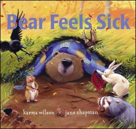 """The cover of the book, """"Bear Feels Sick"""" by Karma Wilson and Jane Chapman. The large bear is underneath a blanket as all the other animals including birds and rabbits gather around to help him feel better."""