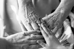 A black and white image of 4 ages of hands touching each other.