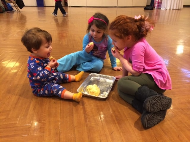An image of three young children, of slightly different ages, sitting around on the floor and sharing some food. They are happy and getting along together.