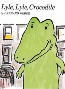 """The cover of the book """"Lyle, Lyle, Crocodile"""" by Bernard Waber. This bright green crocodile stands in front of a building in New York City, smiling."""
