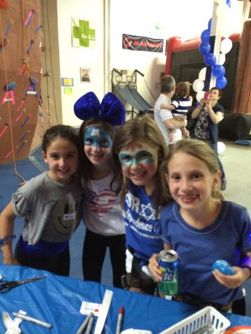 An image of four girls dressed up; some with their faces painted and another big a big blue bow on her head. They are smiling at the camera and embracing each other.