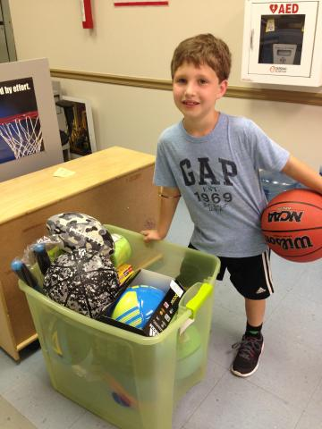 An image of a young boy, probably about 10 years old, holding a basketball and standing next to a bin of an array of sports equipment. He is smiling and looks proud.