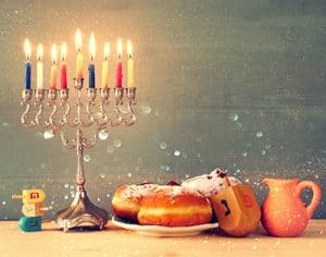 A menorah with all the candles lit, three dreidels sitting next to it and delicious desserts on the other side of the menorah.