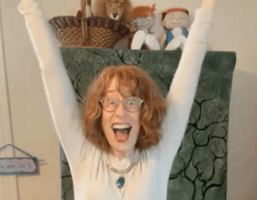 An image of Lisa Litman with her hands straight up in the air, smiling enthusiastically at the camera.
