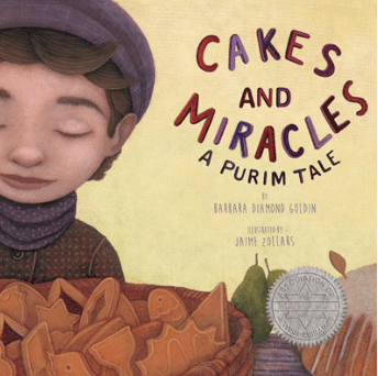 A book cover titled: cakes and miracles: a purim tale, written by Barbara Diamond Goldin and illustrated by Jaime Zollabs. The cover of this book is a young child with their eyes closed holding a basket of purim cookies. They are wearing a hat and scarf and look content.