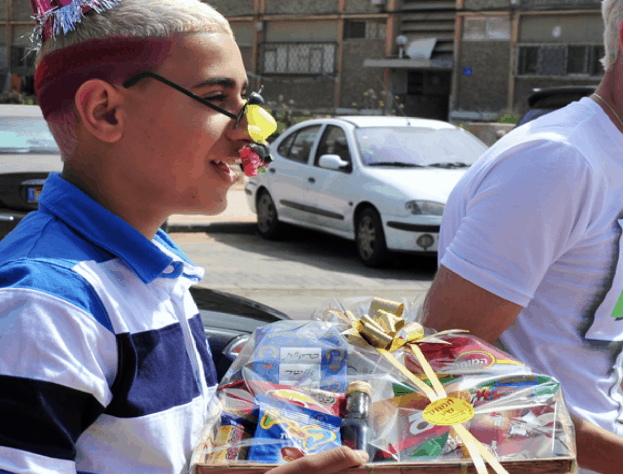 A young boy dressed up in funny clothing with his hair dyed red and white. He is carring a box of goodies and smiling,