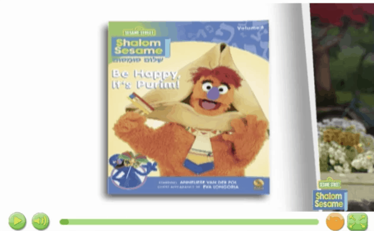 A sesame street book called: Shalom Sesame! Be happy, it's Purim, with an image of a sesame street character peering through a huge hamentaschen that fits around his face!