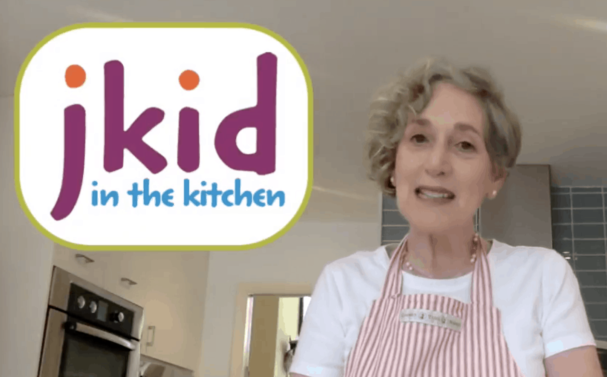 jkid in the kitchen: an image of a woman wearing an apron and smiling, ready to help you make all kinds of delicious foods for shavuot.