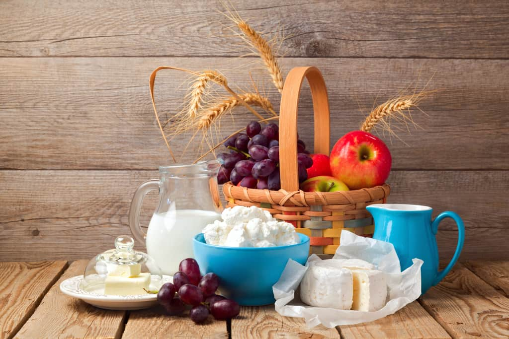 An array of fruits, cheeses, and milk set up in a picnic style to celebrate Shavuot.