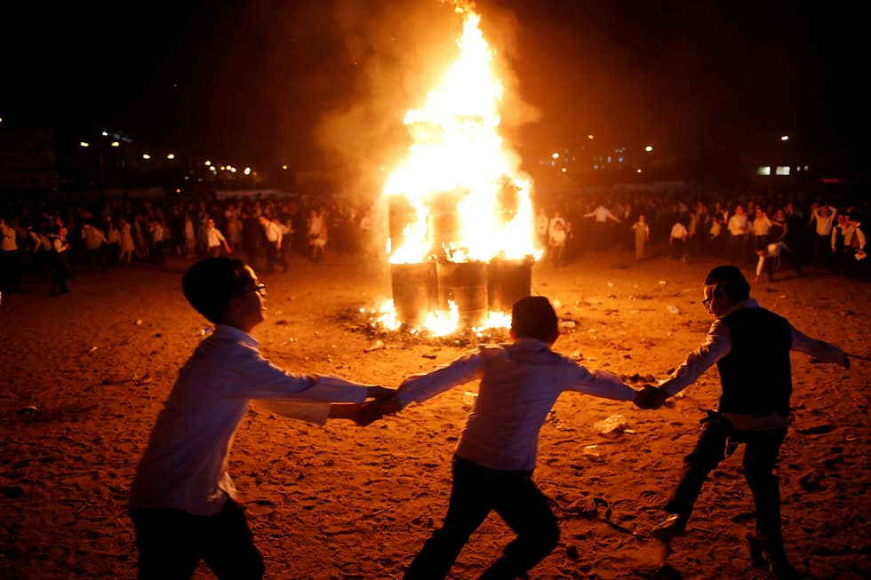People holding hands as they run and dance around a large, flaming, bonfire.