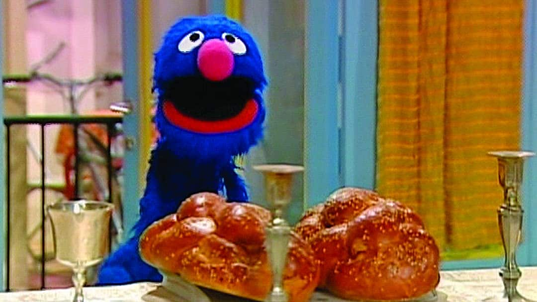 An image of a character on sesame street celebrating shabbat with challah and candles.