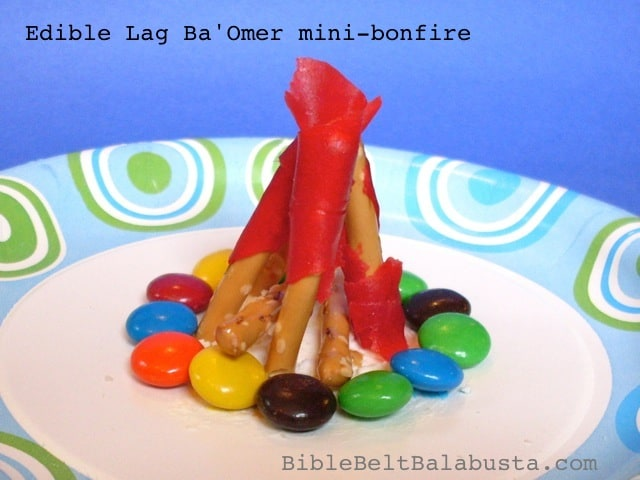 An arts and crafts projects to make an edible campfire: fruit roll ups for the red of the fire, pretzels for the sticks that hold up the fire, and m&m's for the rocks surrounding the base of the fire.