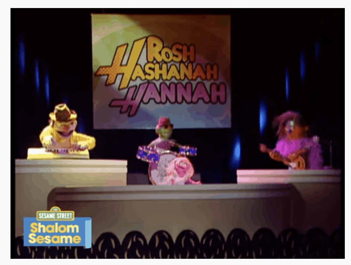 """A screenshot of a Shalom Sesame video. Three muppets are on a stage playing music, with a big sign in the background that says """"Rosh Hashanah Hannah,"""" in a font reminiscent of Hannah Montana."""
