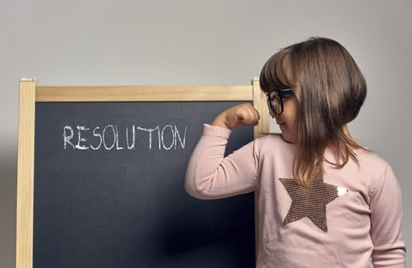 """A young child flexes an arm next to a blackboard that says """"Resolution"""""""
