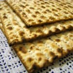 A photograph of three matzah sheets stacked on top of a white lace tablecloth.