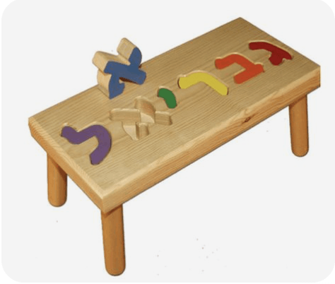 A screenshot of a wooden baby toy. It's a small table with puzzle pieces forming the name Gabriel in Hebrew. Each letter is a different color. The aleph, blue, is lifted out of its puzzle slot.
