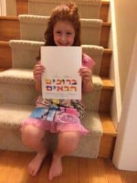 A photograph of a child sitting on carpeted stairs holding a colored sign that says 'welcome' in Hebrew