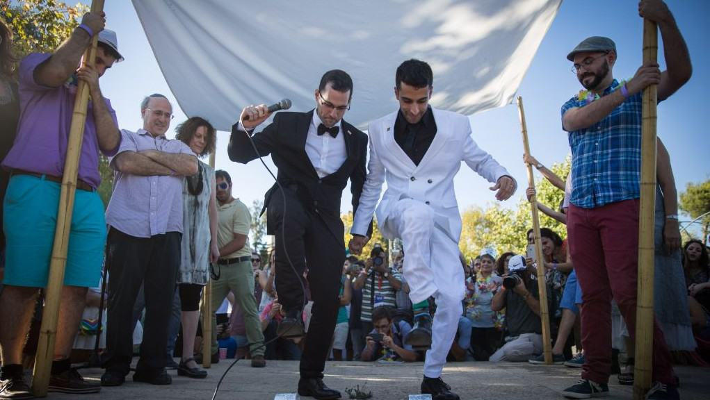 A photograph of a wedding, showing two men in tuxedos smashing a glass underneath a chuppah.