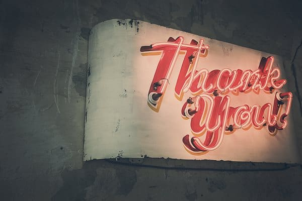 A photo of a nondescript wall that has a giant neon sign that says Thank you!