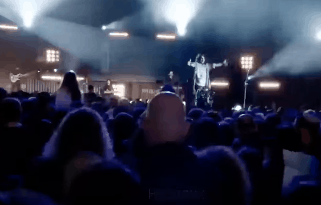 A screenshot from a video showing a crowded concert hall with a conductor gesturing passionately onstage.
