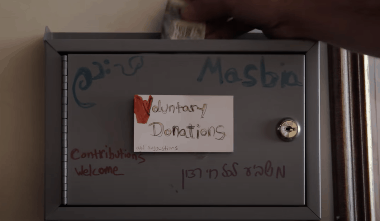 """A screenshot from a video showing a lockbox labeled """"Masbia - Voluntary Donations - Contributions Welcome"""" with a hand putting a dollar into the box."""