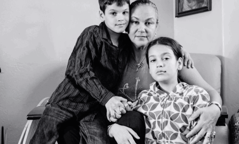 A black and white photo of a family posing together, with a parent and two kids on her lap.