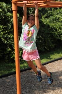 A photo of a young child swinging on a playground structure.