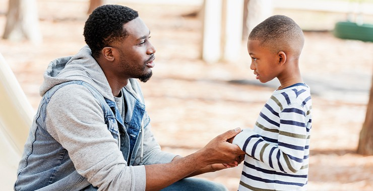 A father crouches down and holds hands with a young child as if they are about to have a serious conversation.